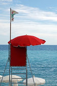 Red lifeguard tower with white flag over clear blue sky — Stok fotoğraf