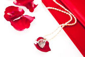 Wedding ring and pearl necklace with red box — Stock Photo