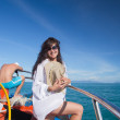 Asian girl sailing on a yacht, man behind her — Stock Photo