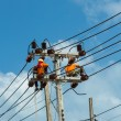 Stock Photo: An electrical power utility worker fixes the power line