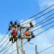 An electrical power utility worker fixes the power line — Stockfoto