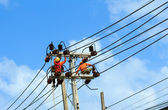 An electrical power utility worker fixes the power line — Foto de Stock