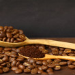 Coffee beans and ground coffee on wooden spoon with grunge backg — Stock Photo #32174123
