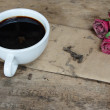 Old paper pink roses and black coffee cup on grunge wood table — Stock Photo #39826599