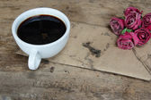 Old paper pink roses and black coffee cup on grunge wood table — Stock Photo