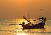 Stunning golden sunset over sea and sky with fishing boat floating — Stock fotografie
