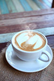 Hearts latte art coffee cup on grunge wood table — Stock Photo