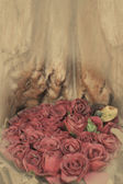 Old paper red roses on grunge wood teak shelf in vintage style — Stock Photo