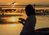 剪影女人拿着咖啡看着海鸥飞在海景日落 — 图库照片