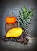Martwa natura owoce dyni, ananasa i mango na drewno deska — Zdjęcie stockowe