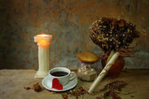 Still life cup of love,candle, dry roses and grunge paper on wooden table — Stock Photo