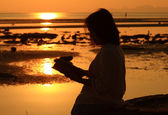 Silhouette woman reading book by beach at sunrise — Stock Photo