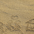 Happy family and house with heart shape drawn on beach sand — Stok Fotoğraf #41246825