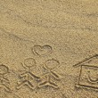Happy family and house with heart shape drawn on beach sand — Stockfoto #41246825