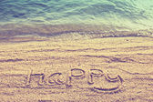 Happy text wrote  on beach sand in vintage style — Stockfoto