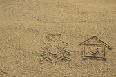 Happy lover and house with heart shape drawn on beach sand — Stock Photo