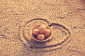 Easter eggs in bamboo basket on beach — Stock Photo