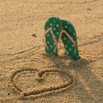 Flip flops and heart shape on sand — Stock Photo #45060873