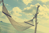 White hammock over blue sea and sky in vintage style — Stock Photo