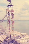 Wind bell shell mobile on resort over ocean in vintage style — Stockfoto