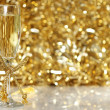 Champagne flutes with golden background - Stock Photo