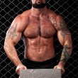 Bodybuilder posing in front of chain link. — Stock Photo #6528320