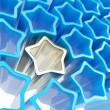 Stock Photo: Silver extruded star among blue ones as background
