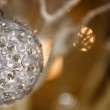 Hanging christmas balls on silver illuminated background — Stock Photo