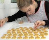 Teen making heart shaped cookies — Stock Photo