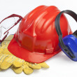 Red safety helmet with earphones and goggles — Stock Photo