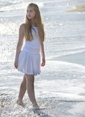 Young woman in white dress walking on the beach. — Stock Photo