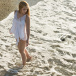 Young woman walking on a white sand beach — Stock Photo