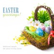 Easter eggs in basket with spring flowers - Stock Photo