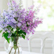 Bunch lilac flowers in vase on table — Foto Stock