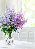 Bunch lilac flowers in vase on table — 图库照片