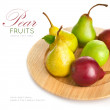 Fresh pears on the wooden plate — Stock Photo #30149929