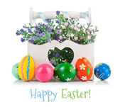 Easter eggs in wooden basket with spring flowers — Stock Photo