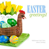 Easter eggs in basket with flowers — Stock Photo