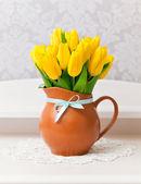 Žluté tulipány váza s modrými luk — Stock fotografie