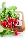 Bundle radish on wooden board with knife — Stock Photo