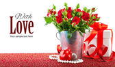 Bunch red roses with gift and heart — Stock Photo