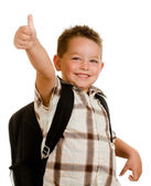 Happy schoolboy wearing backpack and giving thumbs up isolated on white — Stock fotografie