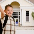 Happy child in front of school wearing back pack and giving thumbs up — Stockfoto
