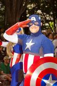 Ein comic-buch-fan, verkleidet als captain america grüßt auf der jährlichen dragoncon-parade — Stockfoto