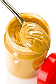 Open jar of peanut butter with spoon — Stock Photo