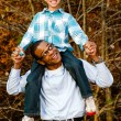 Fall or winter portrait of African-American father and son outdoors at park - Stock Photo