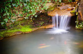 Waterfall spilling into coy fish or goldfish pond — Stock Photo