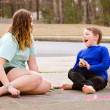Siblings play with chalk drawing in drive way or sidewalk — Stock Photo