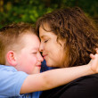 Mother and son hugging with woman kissing child — Stock Photo
