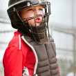 Portrait of child with catcher equipment on during baseball game — Stock Photo